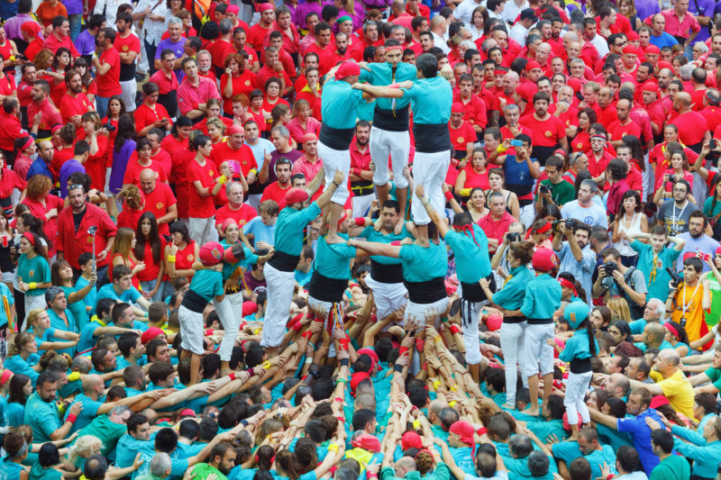 "Tarragona, Spain - October 4, 2014: Members of the ""Colla St.Pere y St.Pau"", build a traditional human tower at the Tarragona during celebrations in Tarraco Square Sand castle contest, October 4, 2014, Tarragona, Spain. A perfect example of teamwork, union and brotherhood."