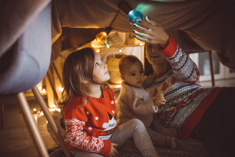 Mother playing under blanket tent with her kids, it's Christmas and they enjoy in time together.